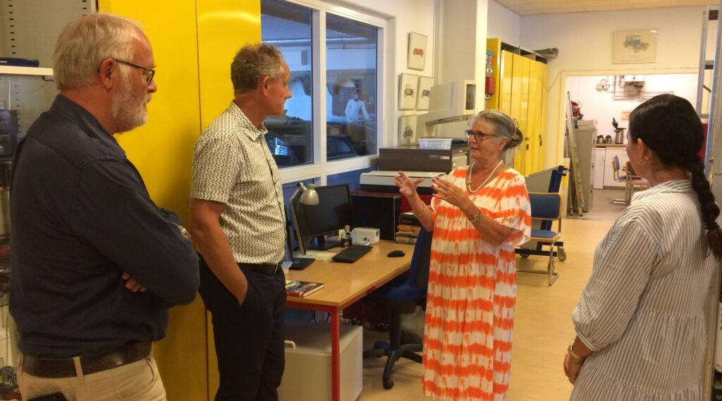 Motorstyrelsens direktør, Jørgen Rasmussen, lytter interesseret da formand for Dansk Veteranbil Klub, Dorte Stadil fortæller om arbejdet med det omfattende bibliotek